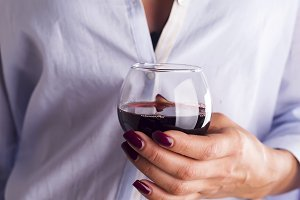 Close-up of woman holding glass of wine
