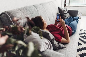 Young woman using smart phone while lying on the couch at home