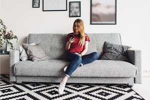 Young woman at home sitting on the couch using smartphone