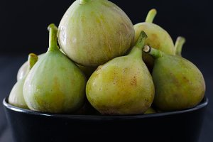 Figs in bowl on black background.