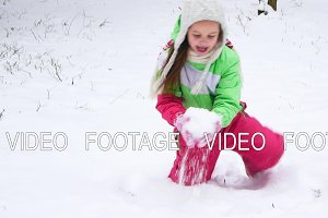 Girl has fun in the winter, throwing a handful of snow up in the air