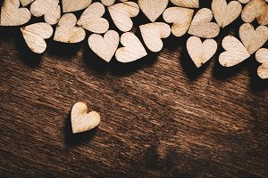 Wooden hearts on dark wooden backgro