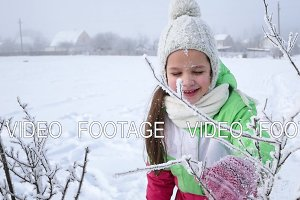 Happy child playing with snow in winter park. Slow motion
