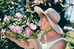 Senior woman smelling flowers on a t