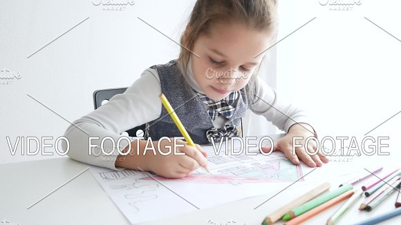 Little girl drawing a picture on white room. 7 years old girl drawing and coloring on a paper at home.