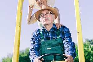 Senior couple riding on a tractor tr
