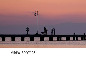 Family walking their dog on a pier