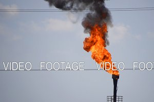 The smoking gas torch. Environmental pollution. Torch system on an oil field