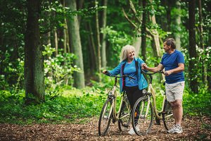 Retired couple walking with bikes