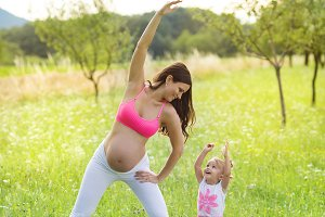 Pregnant woman practicing on the meadow.