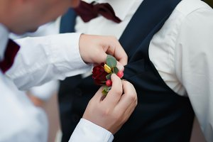 bridegroom is dressed in  buttonhole