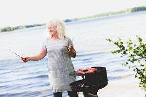 Senior woman barbecuing by the lake.