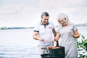 Senior couple preparing sausages
