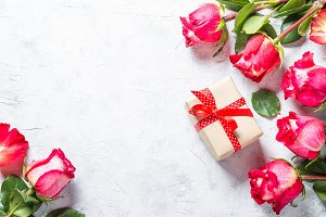 Red rose flower and present box on wooden table.