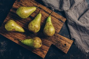 Green pears on an old cutting Board