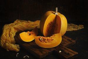 Raw pumpkin cut into pieces on a dar