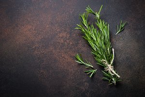 Sprig of Rosemary on dark rusty stone table.
