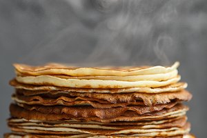 High stack of classic Russian thin pancakes. Rustic style. Traditional for the Russian pancake week Maslenitsa