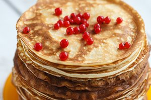 High stack of classic Russian thin pancakes with red currant berries . Rustic style. Traditional for the Russian pancake week Maslenitsa