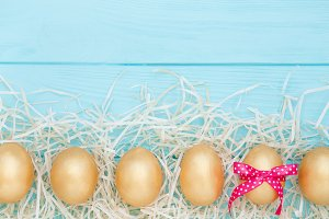 Row of Golden Easter eggs on blue