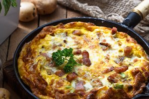 Baked omelette with bacon and cheese in a pan, close view