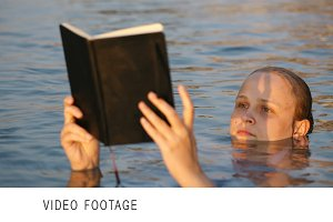 Woman reading while floating