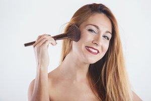 Smiling woman applying make up