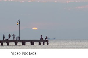 People relaxing on a pier at sunset.