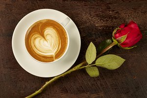 cappuccino with red rose on wood