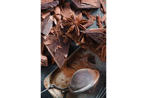 Chocolate pieces with spices and a cocoa strainer on a rustic baking sheet. Dessert food photography. Close-up of sweets.