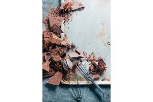 Broken dark chocolate on a concrete background with a cocoa strainer and a whisk with glazing. Rustic baking sheet. Dessert food photography.