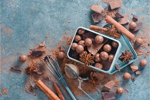 Homemade chocolates and pieces of broken chocolate with spices, anise stars, cinnamon and cocoa on a stone background in a rustic metal box. Confectionery food photography.