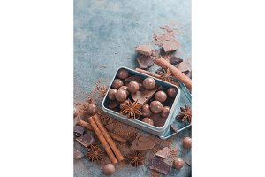Box with an assortment of chocolates and pieces of broken chocolate with spices, anise stars, cinnamon and cocoa on a stone background. Homemade sweets photography.