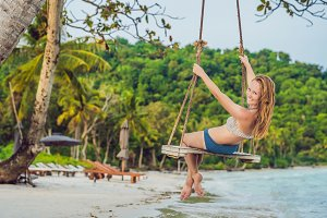 Vacation concept. Happy young woman sitting on swing enjoying sea view