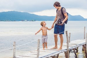 Happiness father and son on the pier at sunny day under sunlight