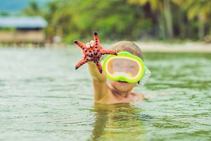 A boy and a red starfish against the backdrop of the sea