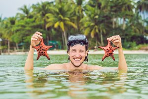 Happy young scuba diver holding sea star, smiling, looking at camera