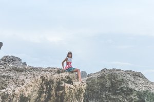 Beautiful young woman sitting on the stone on the seashore. Tropical island of Bali, Indonesia.