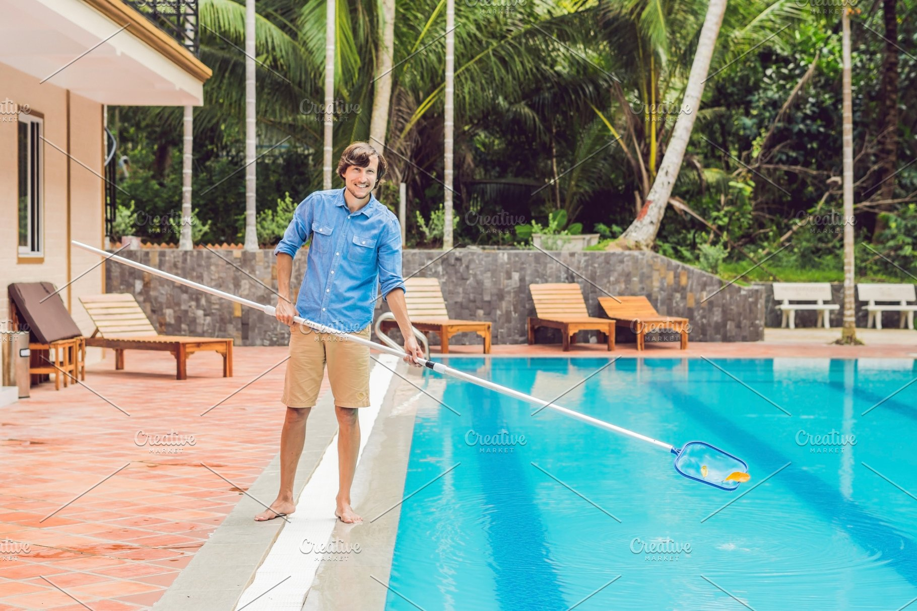 Cleaner of the swimming pool . Man in a blue shirt with cleaning ...