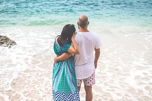 Happy young honeymoon couple posing on the beach. Ocean, tropical vacation on Bali island, Indonesia.