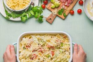 Female hand holding pasta casserole