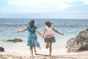 Two women having fun on the tropical beach of Bali, Indonesia.