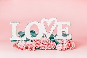 Word LOVE with roses at pastel pink