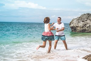 Happy young honeymoon couple having fun on the beach. Ocean, tropical vacation on Bali island, Indonesia.