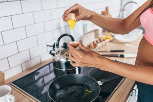 Fit woman in kitchen cracking egg into frying pan.