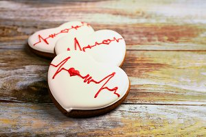 Heart shaped gingerbread cookie on wooden background