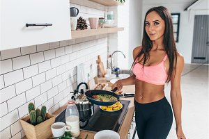 Fit woman holding frying pan with omlette. Prepare healthy food