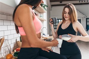 Two fit female friends having breakfast, resting after workout.