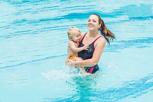 Young mother teach her little son, how to swim in a swimming pool