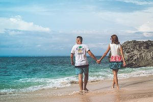 Happy young honeymoon couple walking on the beach. Ocean, tropical vacation on Bali island, Indonesia.
